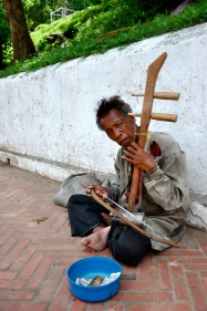 A man plays an instrument in Laos