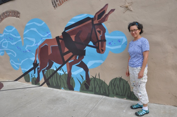 Eurhi Jones with one piece of the mural that represents a time when mules would carry boats along the canal. (Greta Iverson/for NewsWorks)